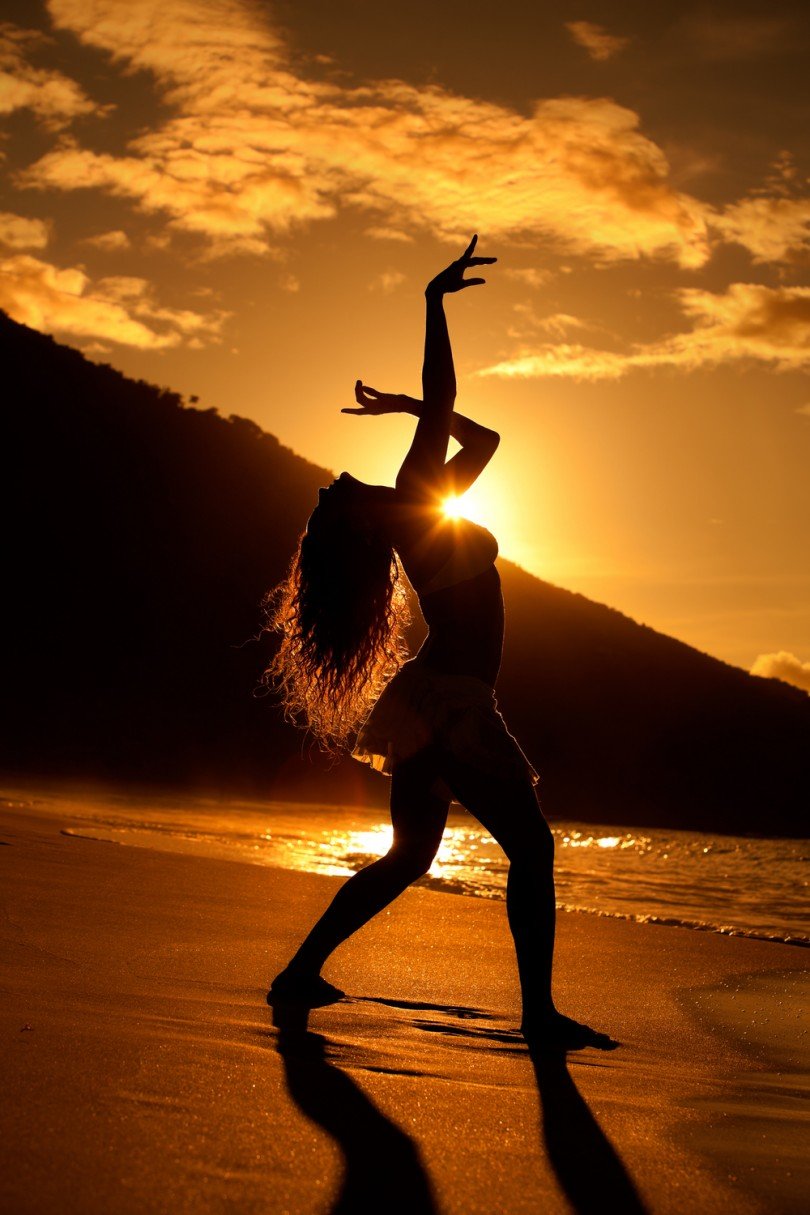silhouette of young woman dancing at the Caribbean beach at sunset